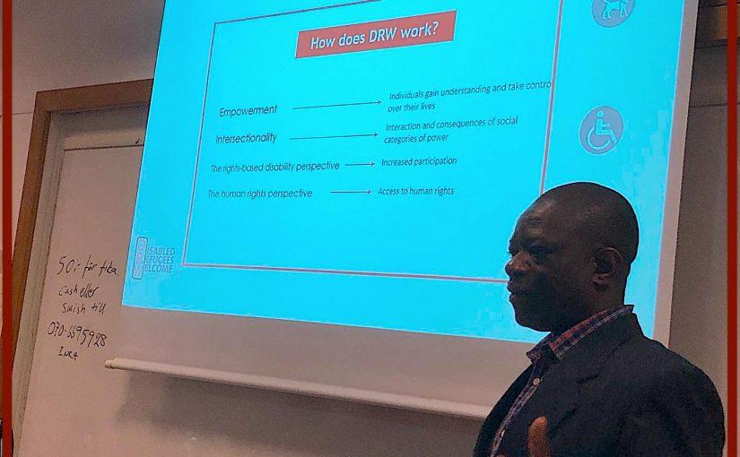 Julius Ntobuah framför en powerpont bild, förklarar hur DRW arbetar